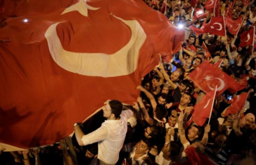People hold Turkish flags in Taksim square in Istanbul on July 16, 2016 during a demonstration in support to Turkish president.