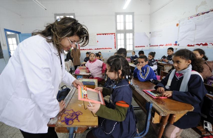 A Tunisian teacher works with her students on March 8, 2011 in Tunis