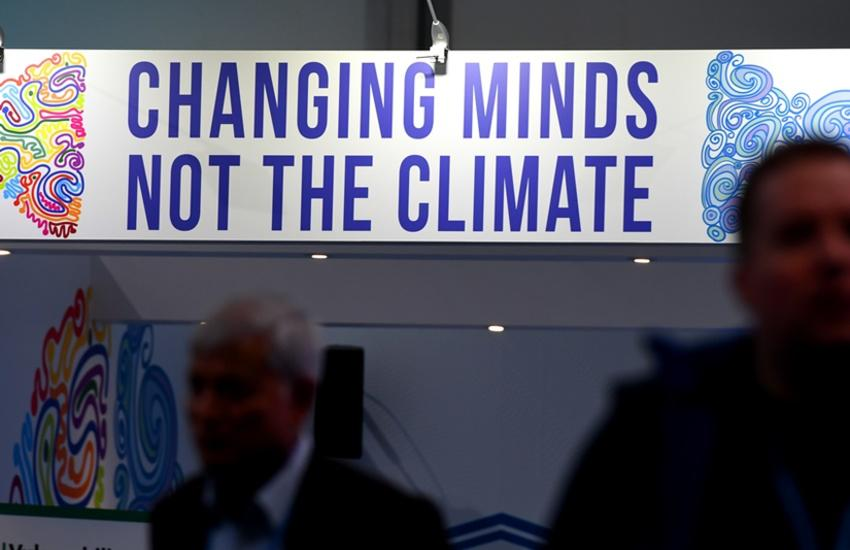 "Visitors stand in front of a banner reading ""changing minds, not the climate"" at a pavillion on November 8, 2017 during the COP23 United Nations Climate Change Conference in Bonn, Germany"