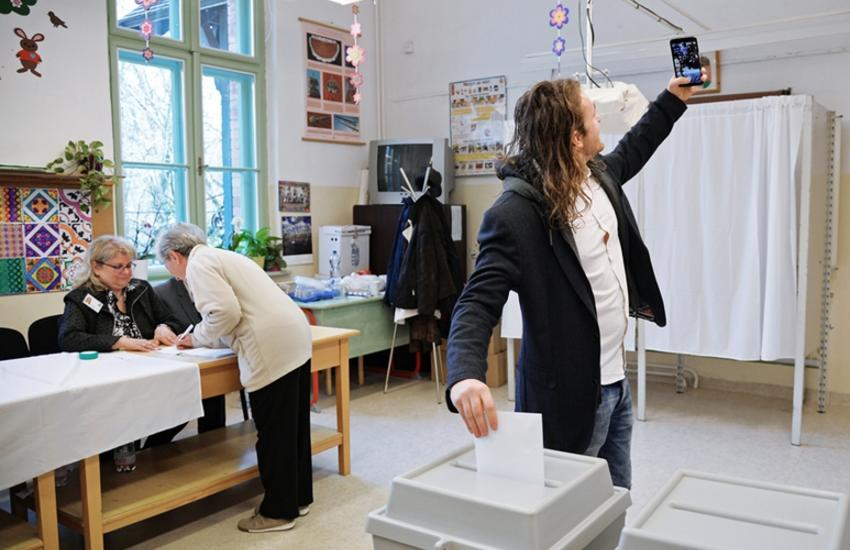 Man taking a selfie at a voting booth
