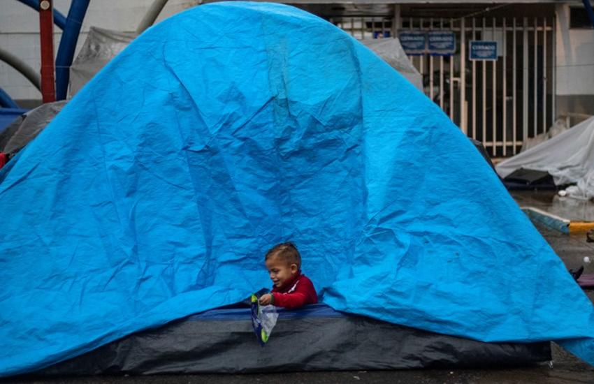 A Central American migrant boy, plays in a tent while camping near a closed temporary shelter a few meters from the US-Mexico border in Tijuana, Baja California state, Mexico, on December 5, 2018