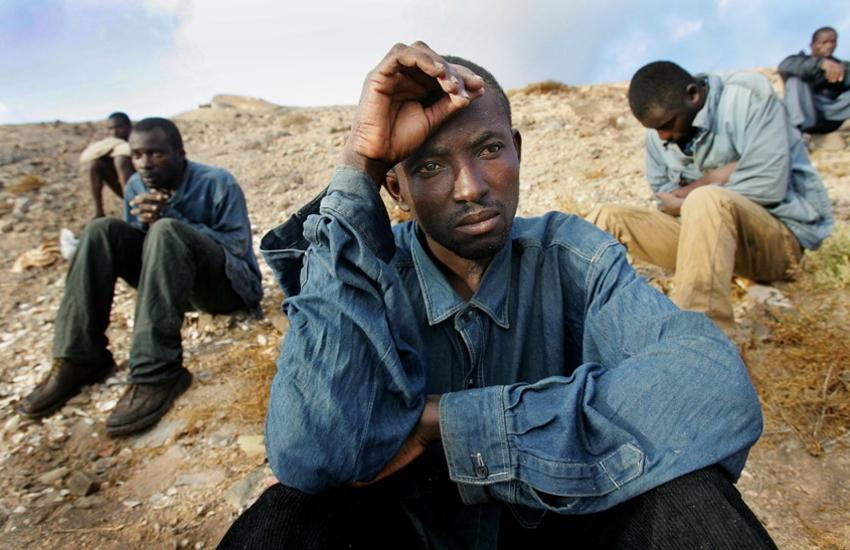 Illegal immigrants rest on a beach after arriving on a makeshift boat in Fuerteventura, one of Spain's Canary Islands, October 10, 2004