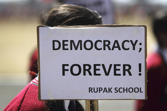 Child holding up sign saying Democracy forever