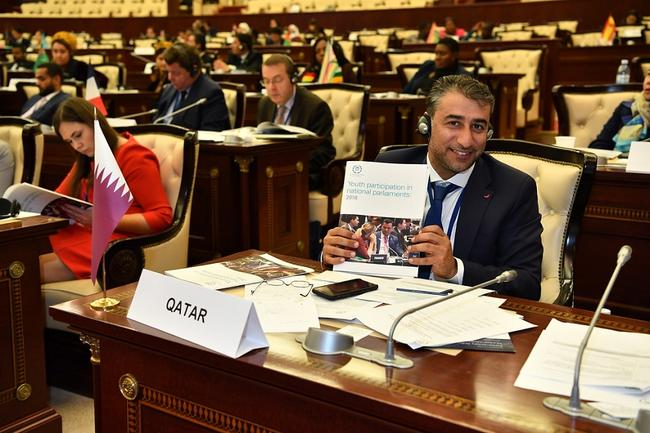 MP holding up an IPU publication at the 5th Global Conference of Young MPs