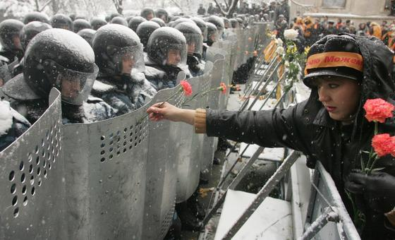 Woman handing rose to soldiers